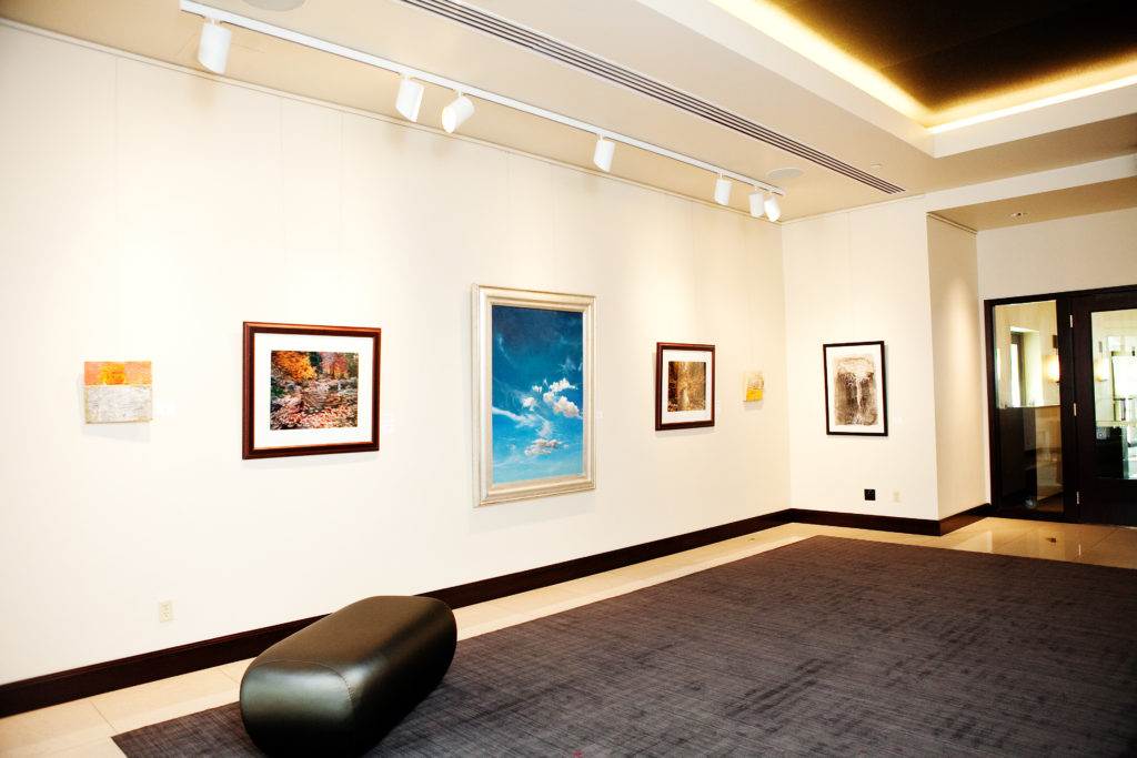 art gallery with painting of blue sky with cloud at center