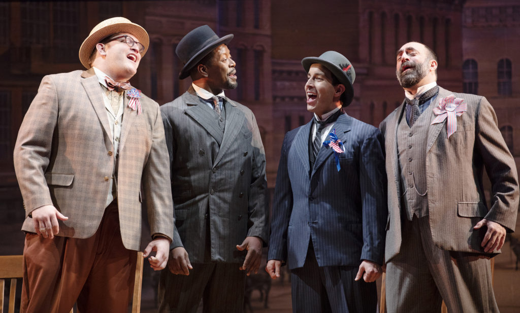 four men singing on stage while dressed in suits with nice hats